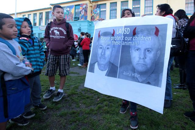 Alumnos sostienen cartel con fotos de los supuestos pederastas.