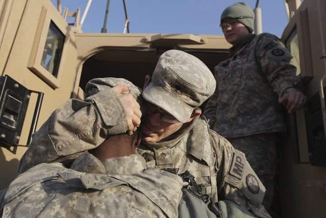 Soldados de la  Primera División de Caballería del ejército de EEUU se abrazan mientras se preparan para partir de la base Camp Ader.