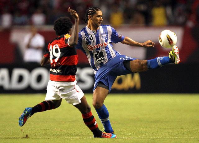 Negueba, jugador del Flamengo  (izq.),  marca a Fernando Giménez, del Emelec de Ecuador, en un pasaje del partido de  ayer jugado en Brasil.
