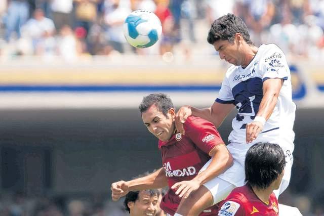 Eduardo Herrera (der.), de  Pumas, cabecea sobre la marcación de  Alejandro Castro, de Estudiantes.
