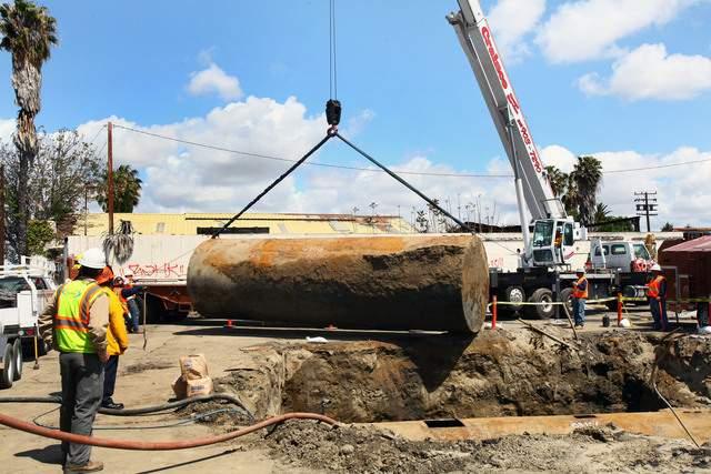 Trabajadores de la EPA retiran un tanque abandonado de 10 mil galones como parte de un proyecto piloto de limpieza ambiental.