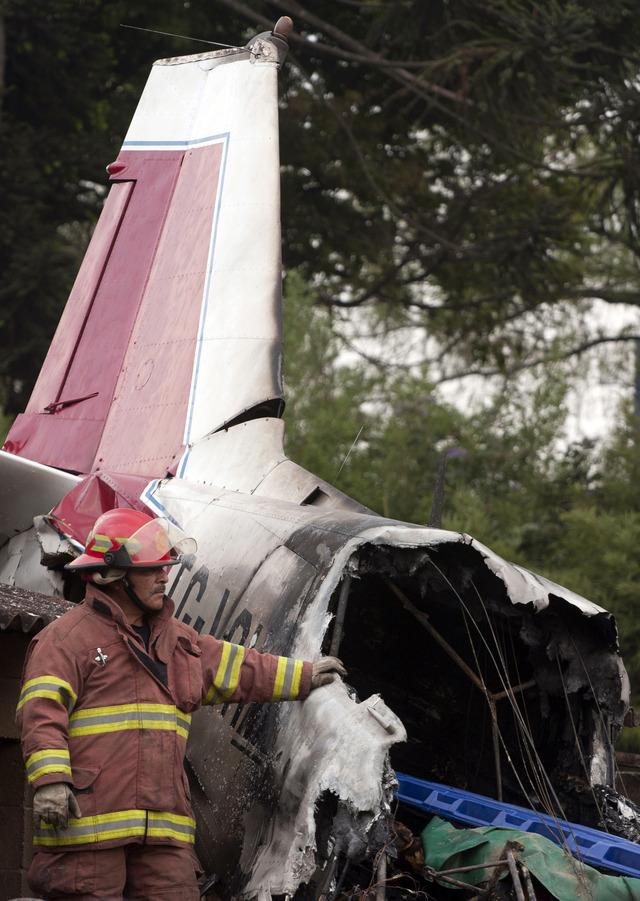 Un bombero muestra los restos de la nave que se accidentó sobre el zoológico, para dejar un saldo trágico.