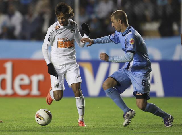 El jugador del Bolívar,  Pablo Frontin (der.), pelea el balón con el delantero de Santos, Neymar, en el duelo de  Copa Libertadores.
