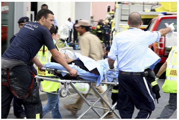 Miembros de los servicios de emergencia trasladan a uno de los heridos en el incendio del centro comercial Vilaggio.