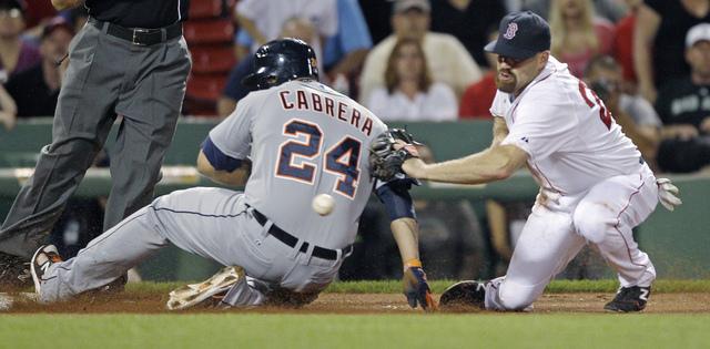 Miguel Cabrera (24), de  Detroit, se desliza en la tercera  base,  y Kevin Youkilis,  de Medias Rojas,  pierde la bola y no puede sacar el out.