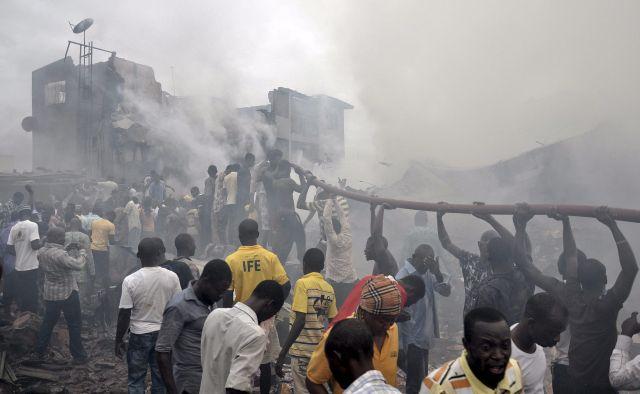 Nigerianos ayudan a sostener una manguera para apagar las llamas en el lugar donde quedaron los escombros de un avión comercial que se estrelló con 159 personas a bordo en Lagos, Nigeria.