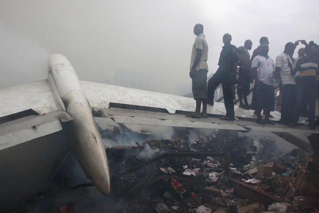 Personas paradas sobre una de las alas del avión que se estrelló sobre un barrio en Lagos.