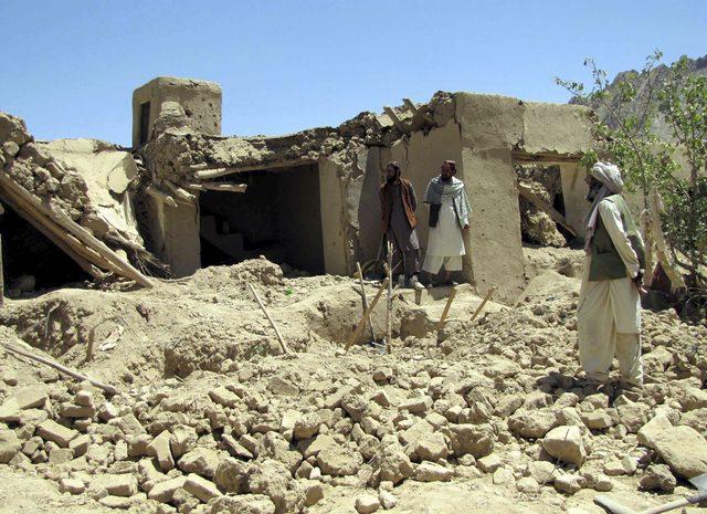 Afganos inspeccionan el lugar tras un ataque aéreo de la OTAN, ayer miércoles, en Logar, Afganistán.
