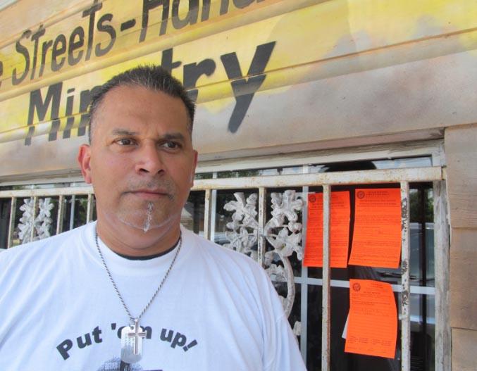 El pastor Roland Nava, al lado de las tres advertencias que el Municipio puso en su ministerio.