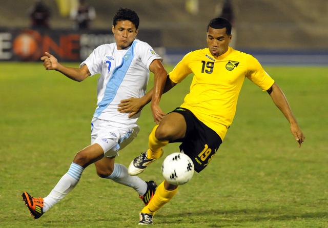 El jamaiquino Adrian Mariappa (der.) controla el balón ante la marca del chapín Jairo Arreola, en acción del partido de anoche en Kingston.
