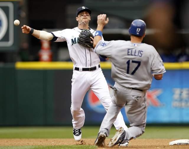 Brendan Ryan (izq.), paracorto de Seattle, elimina en la segunda  a  A.J. Ellis al inicio de un double play.