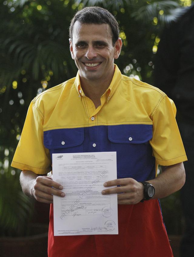 El opositor candidato presidencial, Henrique Capriles, muestra el certificado de registración en la sede del CNE, en Caracas.