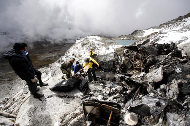 Rescatistas recuperan los cuerpos del helicóptero que se estrelló contra la montaña Mama Rosa, ayer.