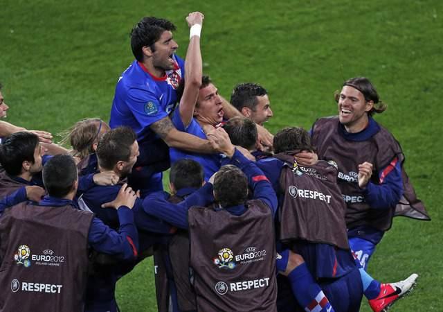 Mario Mandzukic, 'enterrado' por sus compañeros, festeja con el puño en alto después de anotar ayer el 3-1 y su segundo gol sobre Irlanda. Croacia se inyectó optimismo para su partido del jueves contra  Italia.