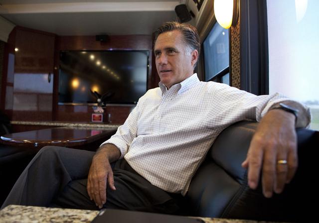 El candidato presidencial Mitt Romney habla con personas de su equipo  en el bus.
