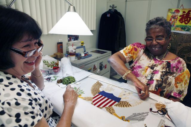 Nereida Rivera (i) y Christine Upchurch, ambas de Filadelfia, bordan a mano una bandera de la Vicepresidencia en la Agencia Logística de Defensa, en Filadelfia.