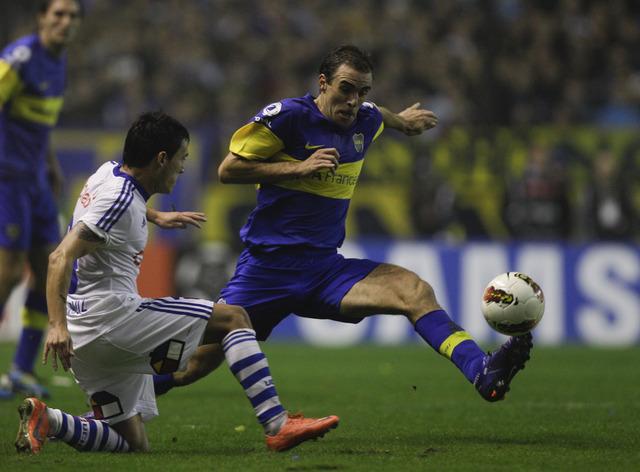 El jugador de Boca Juniors,  Leandro Somoza (der.), pelea la pelota con el defensa de la U de Chile, Charles Aranguiz, en el duelo de ayer.
