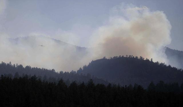 Un aeroplano vuela y atraviesa el humo del fuego de Springer cercano a Lake George, en Colorado.