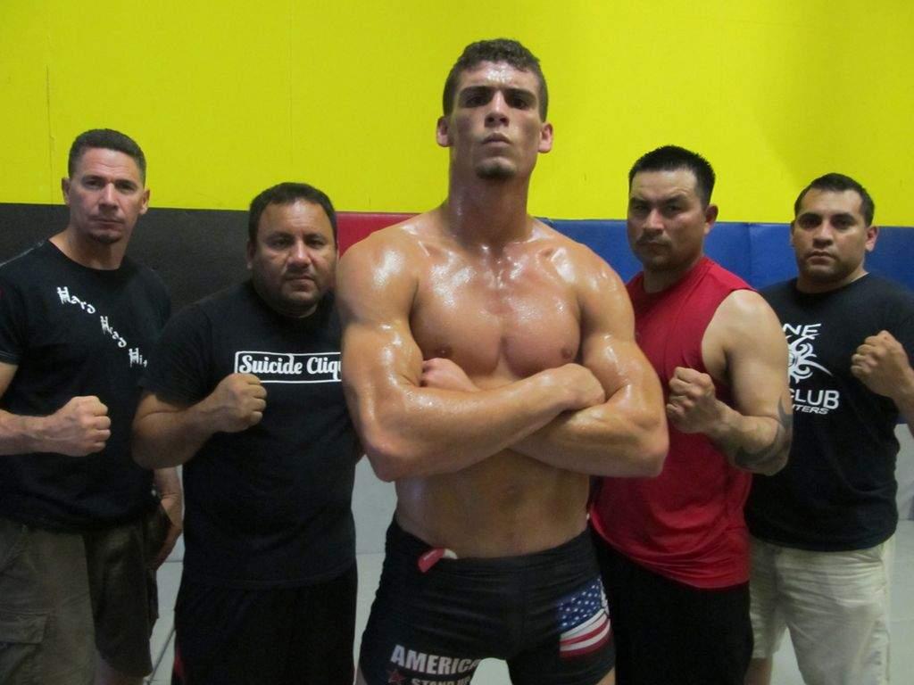 El peleador Charlie Ontiveros (centro) con los entrenadores de artes marciales mixtas de One Fight Club.
