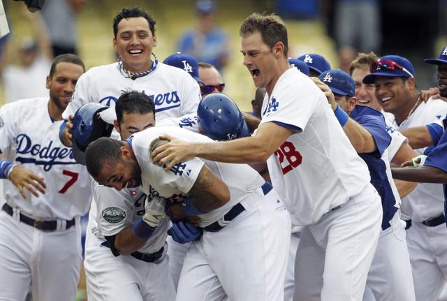 Matt Kemp es recibido eufóricamente por sus compañeros al cruzar el home tras su tablazo que dio la victoria ayer a Dodgers.