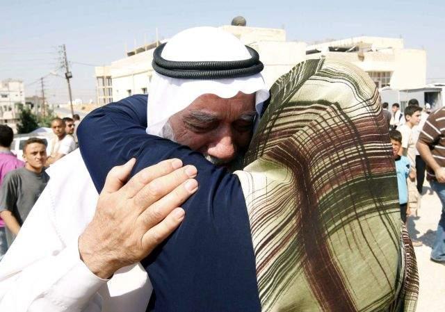 Un hombre sirio abraza a su mujer, tras escapar de la violencia de su país, en el campamento de refugiados de Bashabsheh, en Ramtha.