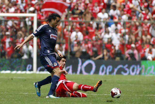 El jugador Juan Carlos Cacho (abajo) de Toluca y Héctor Reynoso (arriba) de Chivas disputan el balón.
