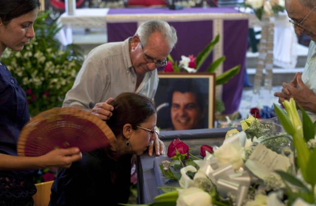 Ofelia Acevedo (segunda a la izq.), viuda del activista Oswaldo Payás, es consolada por un hombre no identificado frente al féretro, en la misa fúnebre que tuvo lugar en La Habana, Cuba,