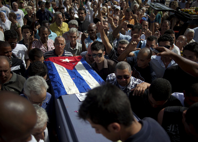 Parientes y amigos del opositor cubano Oswaldo Payá transportan su féretro cubierto con la bandera de su país en el cementerio donde se realizó ayer el funeral en La Habana, Cuba. Payá falleció el domingo en un accidente de tráfico.