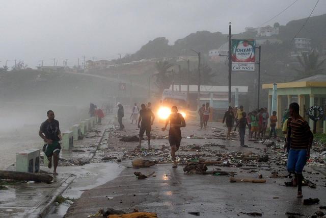 La gente corre sobre un puente golpeado por fuertes olas, debido a la tormenta tropical 'Isaac', en República Dominicana, ayer.