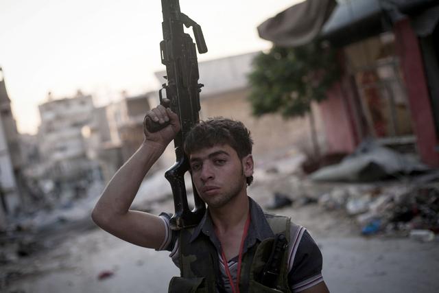 Un soldado opositor al régimen sirio caminaba ayer por una calle del distrito de Amariya en Alepo,  Siria.
