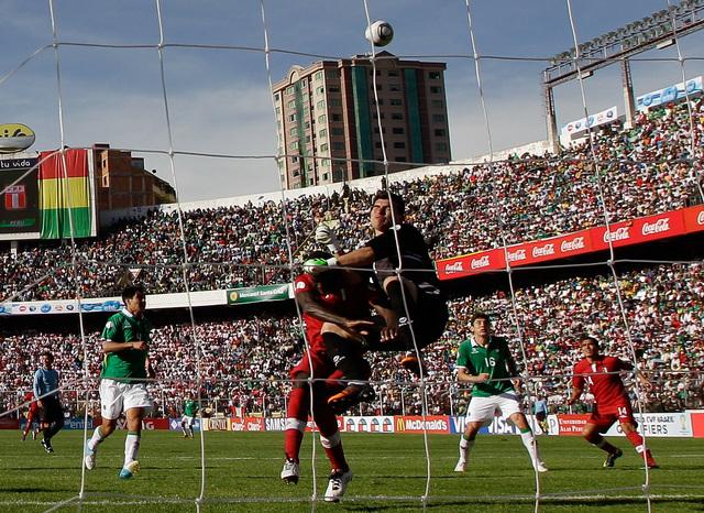 El peruano Christian Ramos pelea una pelota con el portero de la selección de  Bolivia, Hugo Suárez, en el choque disputado en La Paz.