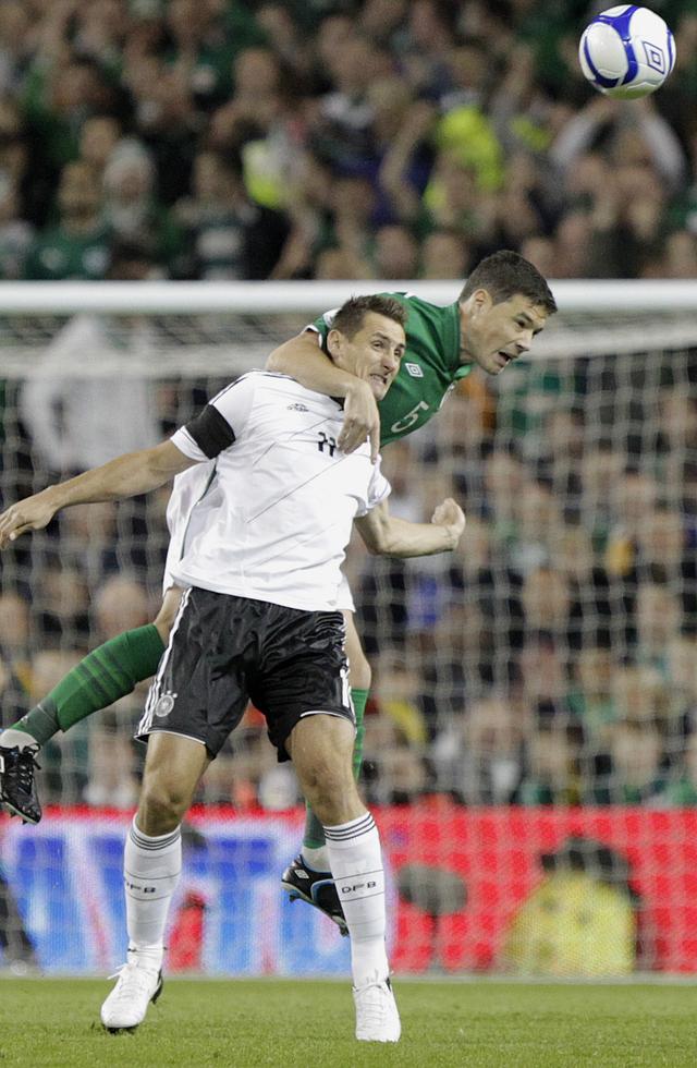 Darren O'dea  despeja el balón antes de llegar a  Klose.