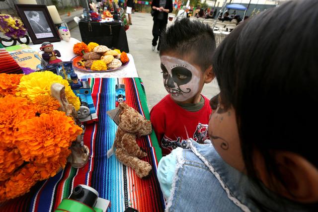 Dos  menores con las caras pintadas miran entretenidos las mesas con los altares levantados por el Día de los Muertos en el Centro del Pueblo, mientras los adultos  aprovechan para inscribirse  para votar.