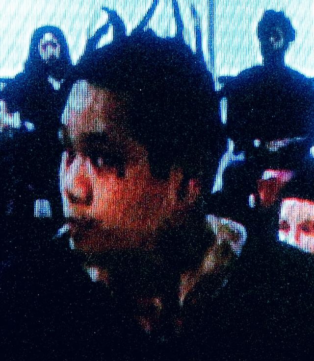 Ka Pasasouk, sospechoso de 4 asesinatos en Northridge, en un monitor de televisión durante su audiencia de extradición en la Corte de Justicia de  Las Vegas.