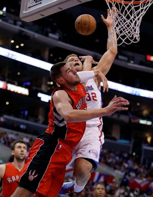 Blake Griffin es fouleado por  Jonas Valanciunas (izq.) de Toronto, en el primer período del juego de ayer.