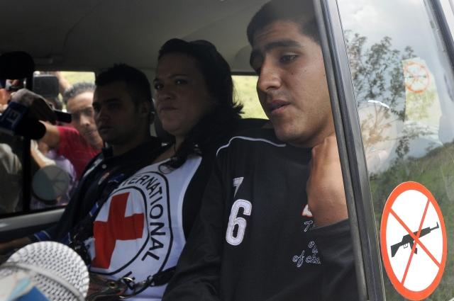 Los policías colombianos Víctor Alfonso González (izq.) y Cristian Camilo Yate (der.) pasan junto a la prensa  ayer, luego de ser liberados.