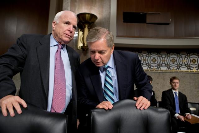 Senadores John McCain (R-Ariz) y Lindsey Graham (R-CS) conferencian en audiencia del Comité de Servicios Armados del Senado, ayer.