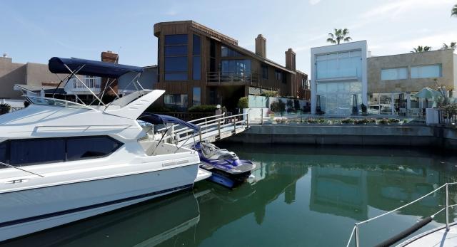 Un bote de lujo y un 'jet ski' se encuentran anclado en un muelle privado cercano a la casa (der.) perteneciente a la familia de la líder sindical Elba Esther Gordillo, en Coronado, California, ayer.