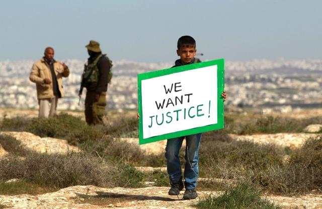 Un soldado israelí rompe una pequeña protesta de palestinos por tierras confiscadas para colonización judia de Sosia, en  la Franja de Gaza.