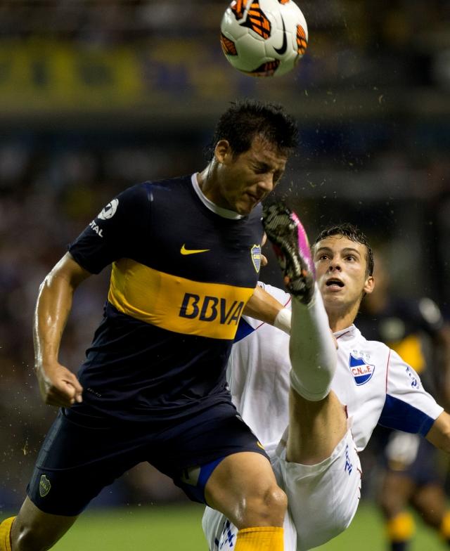 Gonzalo Bueno (der.), del Nacional, le muestra los tachones a Claudio Pérez, del Boca, en acción del juego de ayer en La Bombonera.