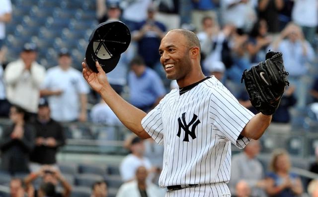 El cerrador de los Yankees, Mariano Rivera, saluda a los aficionados tras lograr el salvamento 602 de su carrera.