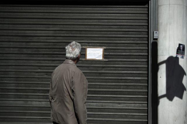 Una persona observa un cartel colocado en una sucursal cerrada del Banco Popular chipriota en las calles de Atenas, Grecia.