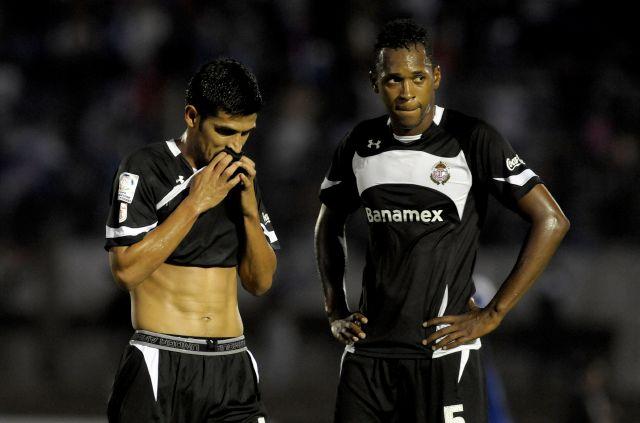 Francisco Gamboa (i), y Matías Wilson, de Toluca,  al final del partido de la Copa Libertadores de fútbol contra el Nacional de Uruguay en Montevideo, Uruguay, en el que Nacional ganó 4-0.