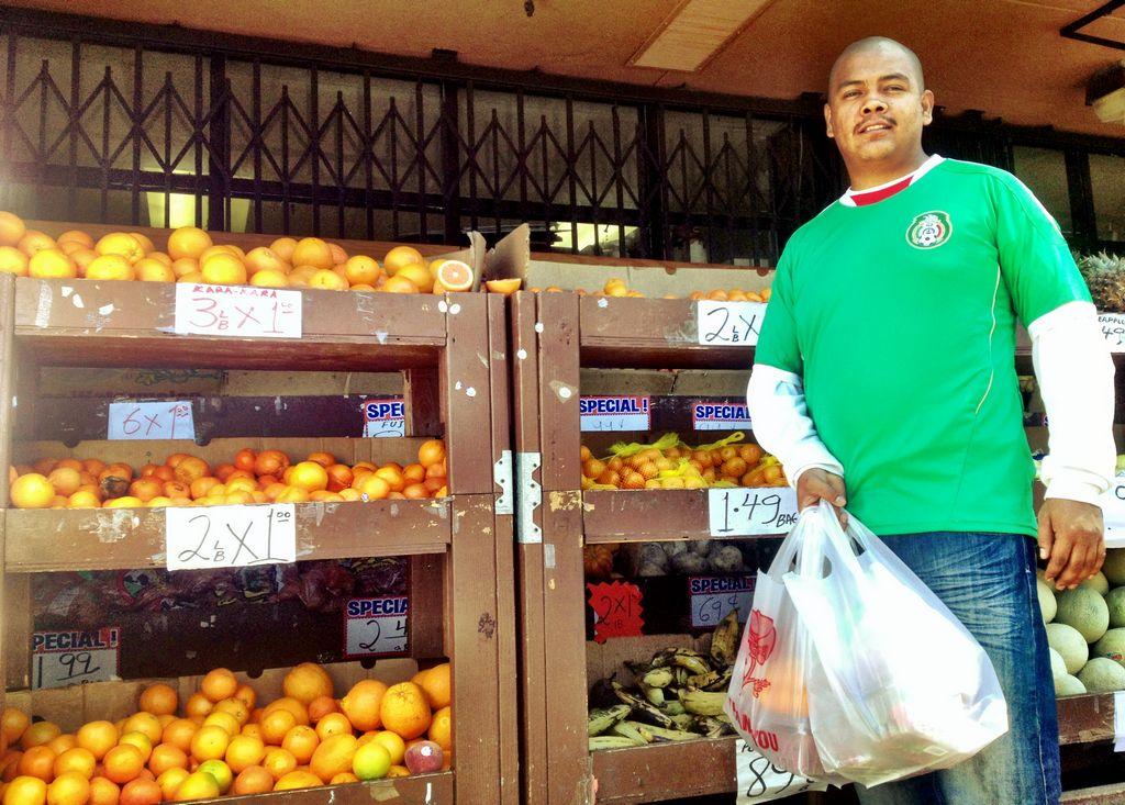 Aficionado a la selección mexicana de compras en barrio de la Misión; la ciudad de San Francisco obliga  a consumidores pagar extra por bolsas de plástico.