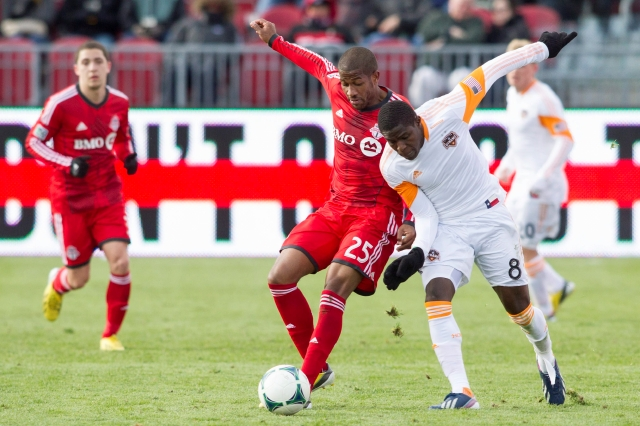 Jeremy Hall (izq.), autor del gol de Toronto,   aguanta la carga de  Kofi Sarkodie del Dymano de Houston durante el partido que terminó 1-1.