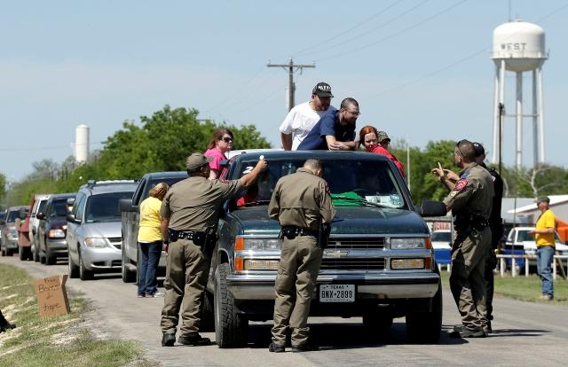 Residentes desplazados esperan en un punto de control por permiso para regresar a sus hogares, tres días después de la explosión, ayer.