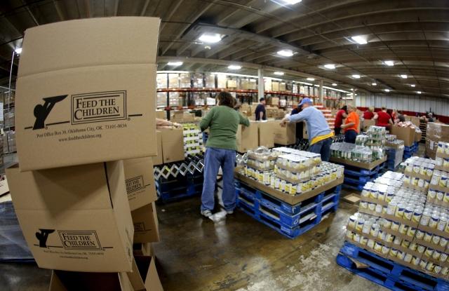 Varios voluntarios llenan cajas con alimentos perecederos en un centro de distribución de Oklahoma.