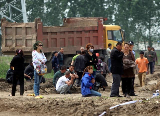 Residentes observan los esfuerzos de rescate en la granja avícola que se quemó y en la cual hay posiblemente más de 120 personas fallecidas, en Jilin, al noreste de China.