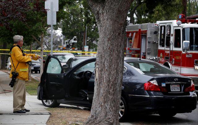Un investigador verifica el auto donde una mujer fue hallada con una herida de bala, en una zona cercana a la universidad.