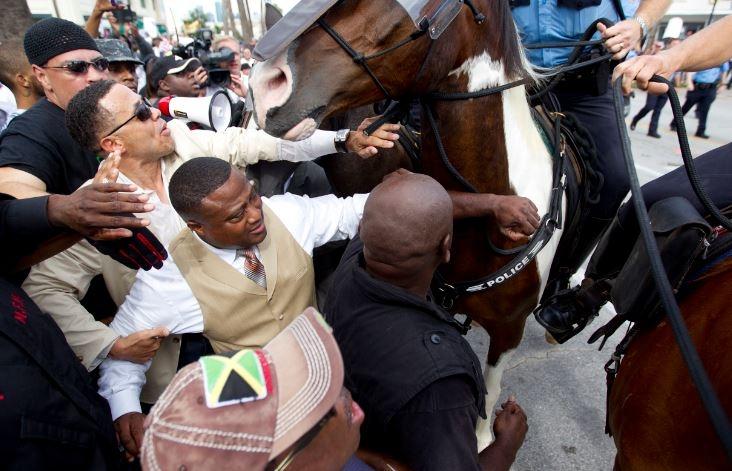 Activista de Houston Quanell X, centro, y otros son empujados hacia atrás por la policía.